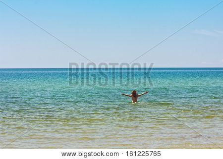 Seashore azure. In the water back to the camera man standing arms outstretched to the sides. Man is free. He has long hair, bronze tan. It should be warm, clear weather. Sea blue. The sky is clear blue with no clouds. The clear line of the horizon.