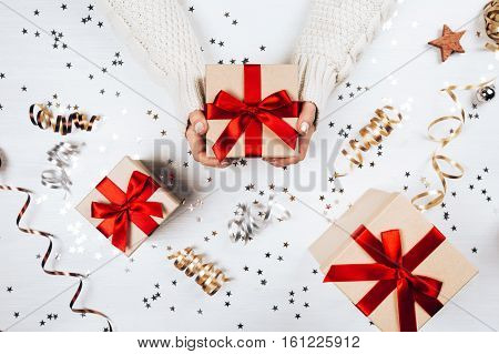 Female hands holding present with red bow on white rustic sparkling background. Festive backdrop for holidays: Birthday, Valentines day, Christmas, New Year. Flat lay style