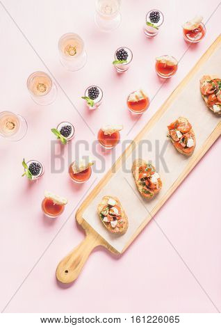 Catering, banquet, party food concept. Snacks, brushettas, gazpacho shots, desserts with berries on corporate event, christmas, birthday, wedding celebration over pastel pink background, top view