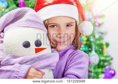 Closeup portrait of a cute little baby girl wearing red Santa hat near festive decorated Christmas tree, with love holding in hands her soft snowman toy, enjoying Xmas present, happy winter holidays