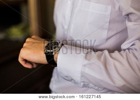 watch on a man's hand the fees of the groom wedding preparation preparation for work putting the clock on the hand fasten clock watch time