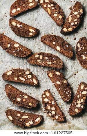 Close-up of dark chocolate and sea salt Biscotti with almonds on baking paper, top view, vertical composition