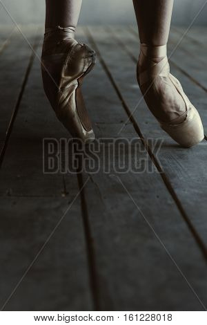 Stretching before the performance. Skillful concentrated involved ballet dancer demonstrating her legs while standing isolated on the tiptoes in pointes on the black colored floor and stretching