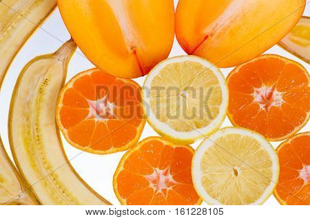 Persimmon tangerine banana lemon on a white background fruits