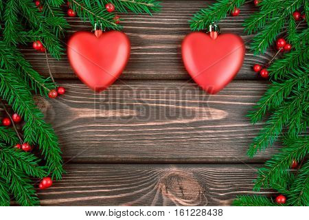 New year Christmas background with fir branches and red toys in the form of a heart