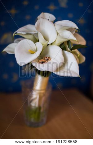 gold wedding rings lie on a bouquet of calla lilies calla bouquet rings on a light background
