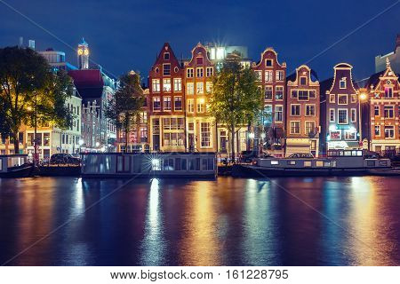 Amsterdam canal Amstel with typical dutch houses and houseboats with multi-colored reflections at night, Holland, Netherlands. Used toning