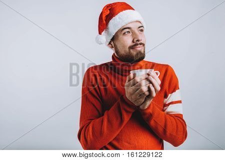 Winter concept - Christmas holiday. Delighed guy in Santa's hat is holding tea cup and imagining his winter holidays
