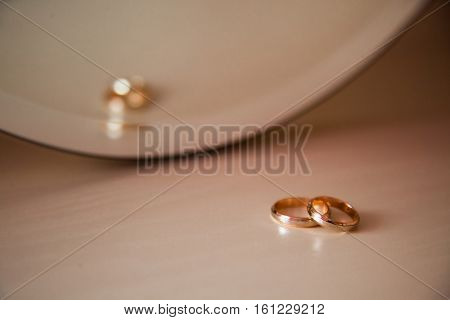 gold wedding rings wedding bands on a yellow background rings on the couch ring in front of mirror