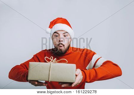 Handsome man in red sweater and Santa's hat holding a christmas gift. Young guy is wondering what is inside of present box. Isolated on white background