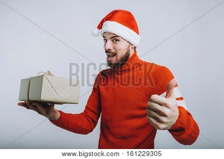 Handsome man holding a christmas gift in one hand and showing that everything is ok or cool with another. Attractive guy is wearing Santa's hat and soft red sweater. Isolated on white background