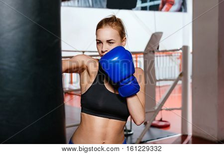 Powerful kick. Intent athletic blonde woman in a gym working on her punch with a punch bag while being very serious