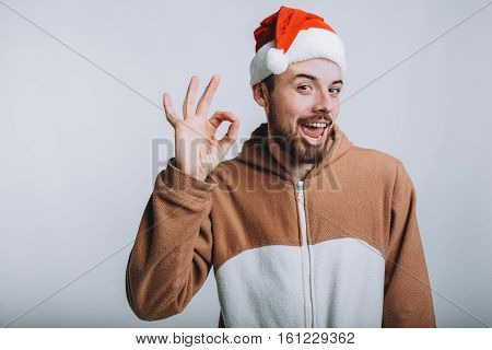 Young handsome man with noel or santa hat. Attractive man is wearing pajamas or fancy dress and showing at camera that everything is ok. He is saying ok with his facial expression. Isolated on white background