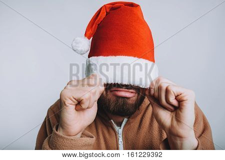 Young handsome man with noel or santa hat. Comic funny man has pulled on his red hat with both hand. Isolated on white background