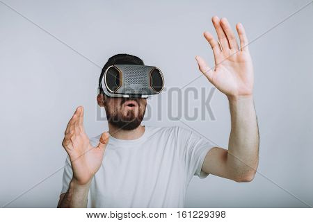 Young man trying vr goggles and imagining virtual reality doing different moves with hands. He is surprised because of seeing something marvellous. Isolated on white background