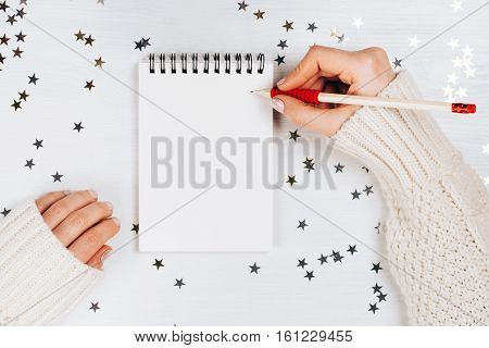 Holiday decorations and notebook with wish list on white rustic table, flat lay style. Planning concept.