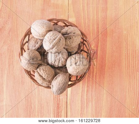 Walnuts in a basket on wooden background.
