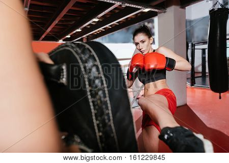 Kick at the right angle. Attractive healthy young woman working on her punch while using her friends help in a gym