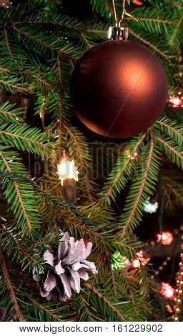 Christmas ball hanging on a branch tree. A bump on the branch and Christmas tree garland