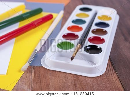 watercolors colored sheets of paper markers and brushes on a wooden surface
