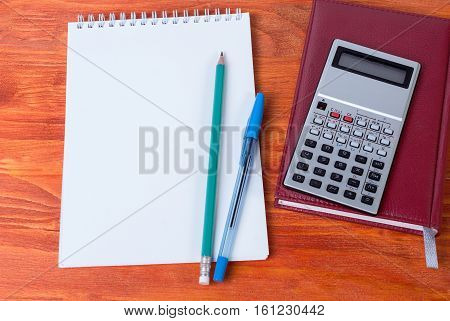 Lying on the table a diary pen and calculator. Business accessories