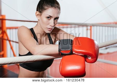 It was a nice work out. Attractive tired fit girl relaxing after the training by leaning on the ring ropes while still wearing boxing gloves