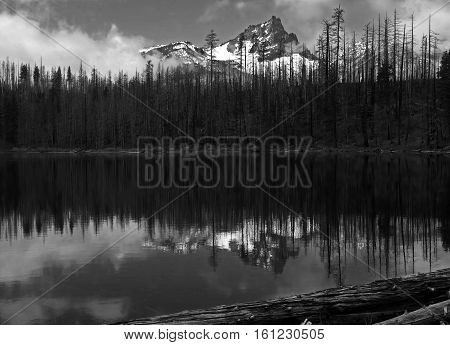 The snow covered Cascade Mountains reflect in Round Lake in Oregon's Mt. Jefferson Wilderness along with low hanging clouds on a fall day.