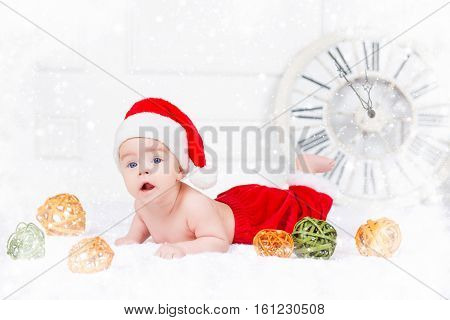 Funny Christmas baby in Santa Claus costume lying on white background.