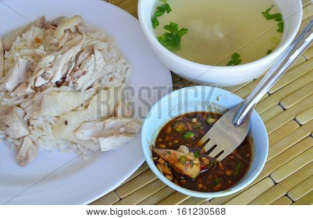 steamed chicken stab in fork dipping spicy sauce