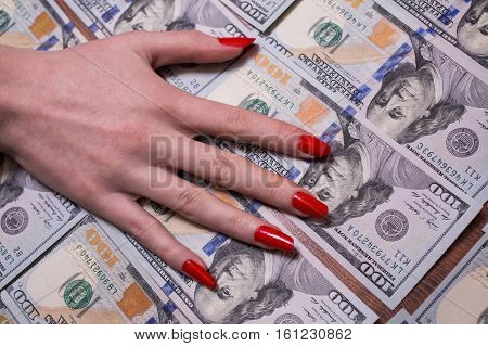woman's hand with red nails lying on the money greed for money background of the money hundred dollar bills front side. background of dollars new hundred-dollar bil face the evolution of the bill in one hundred dollars