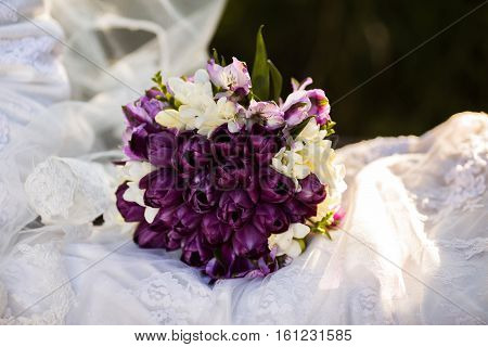 bunch of white and purple flowers lying on a wedding dress on a white background wedding accessories wedding preparation