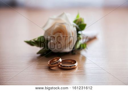 golden rings and wedding boutonniere of white roses on the table gathering groom