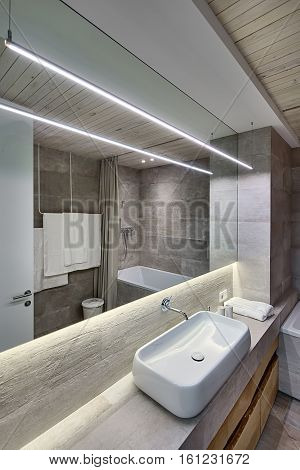 Contemporary bathroom with textured tiles and a wooden ceiling. There is a white sink on the rack, faucet, wooden lockers, mirror, towel, bath, door, wooden panel over the sink, glowing lamps, bucket.