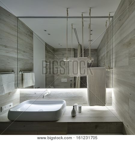 Stylish bathroom with wooden walls. There is a white sink on the rack, faucet, mirror, towel holders, door, wooden panel over the sink, bath cosmetics. Light glows under the mirror.