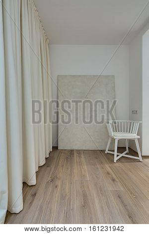 Room in a modern style with white walls and a parquet on the floor. There is a white chair with a pillow, light curtains, switch with power sockets. Vertical.