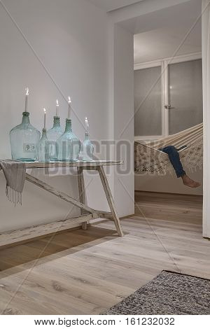 White burning candles in the stylish bottles and a shawl near them on the wooden table on the white wall background. There is a person in the hammock on the window background. Vertical.