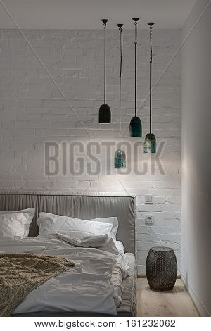 Fancy bedroom in a modern style with white brick wall and a parquet on the floor. There is a bed with a white pillows and a blanket and a brown plaid, lampshade, glowing hanging lamps. Vertical.
