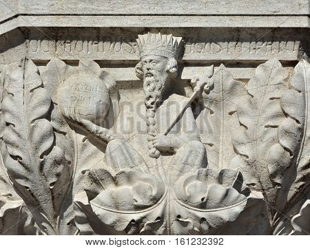 Augustus emperor relief as medieval king with scepter and globe on doge palace capital in Venice