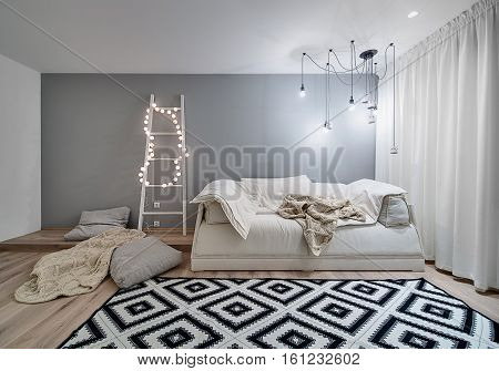 Room in a modern style with white and gray walls and a parquet with a carpet on the floor. There is a sofa, plaids, pillows, wooden ladder with sphere glowing lamps, hanging lamps and decorative owls.
