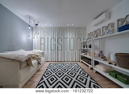 Bright kids room in a modern style with a parquet and a carpet on the floor. There is white shelves on the wheels with toys, boxes, pillows, baskets, buckets, decorative letters, sofa, plaid, lamps.