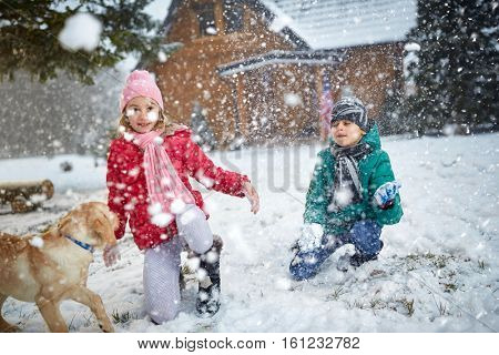 smiling children playing on snow with dog in winter holiday