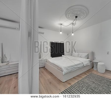 Contemporary bedroom with white walls and a parquet with a carpet on the floor. There is a bed with white pillows and blanket, design nightstands, hanging glowing lamps, bass-relief, mirror, curtains.