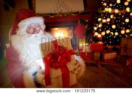 Santa Claus opening a magic gift box and let out atmosphere of a Christmas
