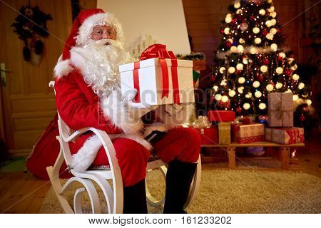 Santa Claus with big box with gift in arms