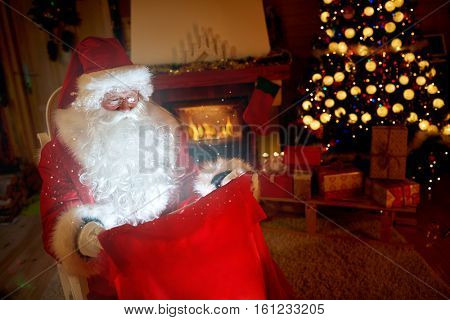 Santa Claus look at red magical sac with gifts