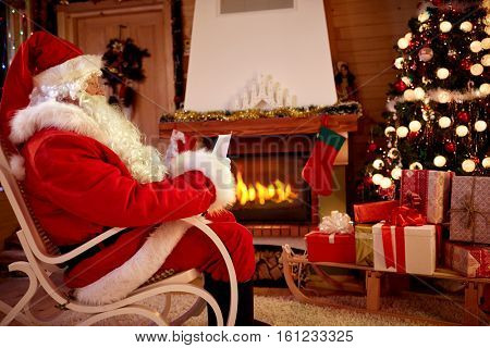 Santa Claus in room near fireplace read children whishing list for Christmas gift