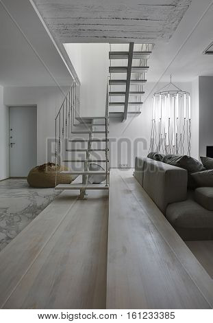 Room in a modern style with white walls. There is a white wooden stair with a metal railing, gray sofa with pillows, glowing tube lamps, brown pouf, door, big lamp under the stair. Vertical.
