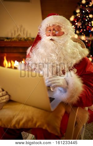 Real Santa Claus using laptop to communicating with children, modern Christmastime
