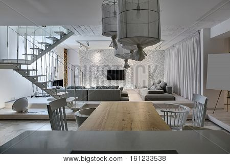 Modern interior with white walls. There is a white wooden stair with a metal railing, gray sofas with pillows, glowing lamps, tables with chairs, TV, walls decorated with firewood and pebbles.