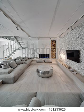 Contemporary interior with white walls. There is white stair with a metal railing, sofas with pillows, sparkle pouf, burning candlesticks and fireplace, TV, walls decorated with firewood and pebbles.